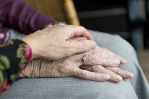 Iemand houdt de hand vast van een ouder iemand