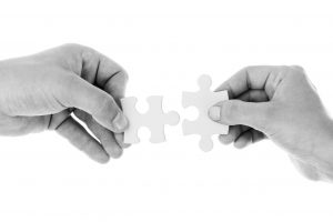 Samenwerken: handen die twee puzzelstukjes ineen schuiven