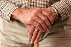 Handen van een oude man die leunen op een wandelstok