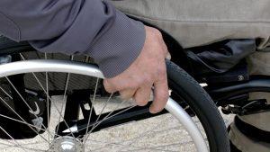 Deel van een rolstoel met een hand op de band van de rolstoel