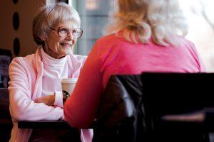 Oudere vrouw in gesprek in een café