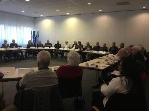 een grote kring van senioren achter een tafel die samen vergaderen